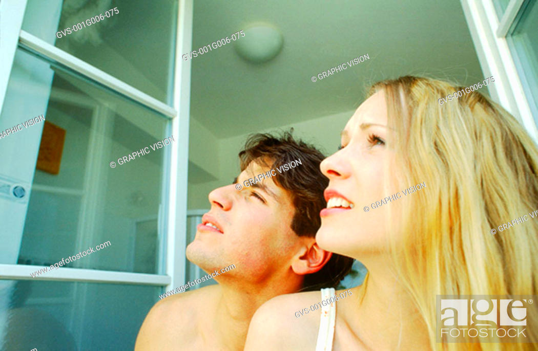 Stock Photo: Young couple at the window looking up.