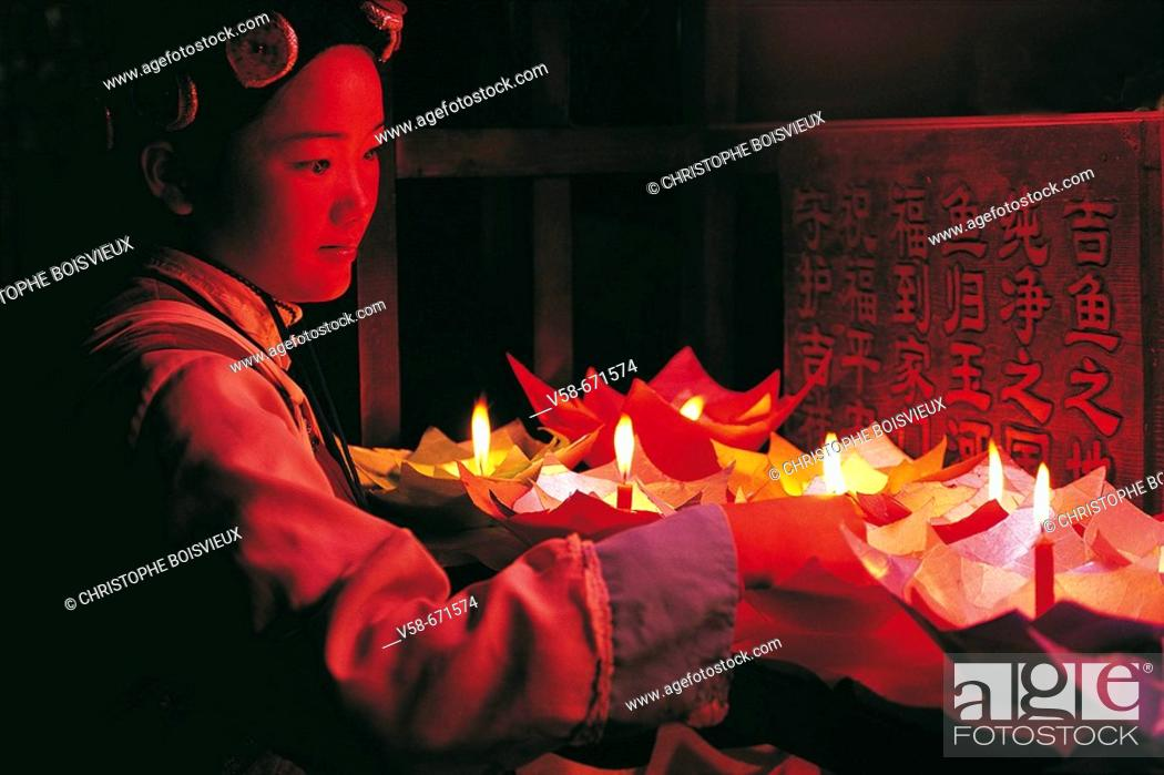 Stock Photo: NAXI WOMAN LIGHTING CANDLE LANTERNS MEANT TO BE FLOATED DOWN THE CANALS, LIJIANG, CHINA.