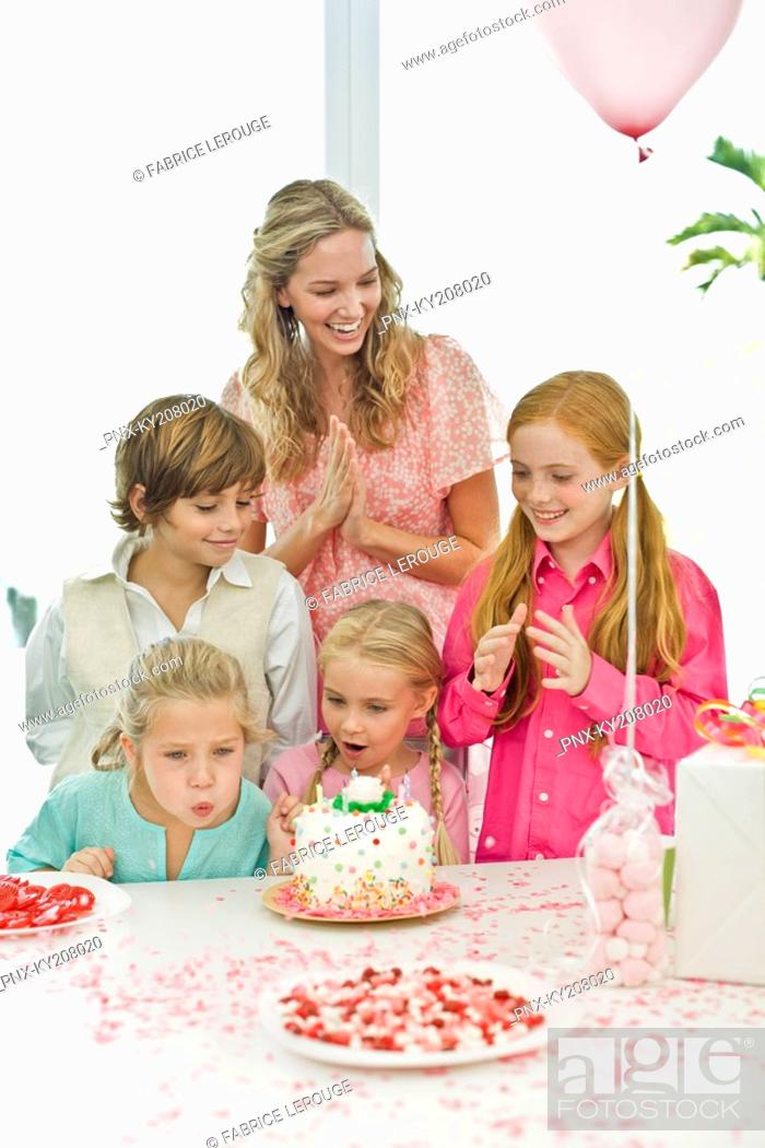 Stock Photo: Girl celebrating her birthday with her mother and friends.