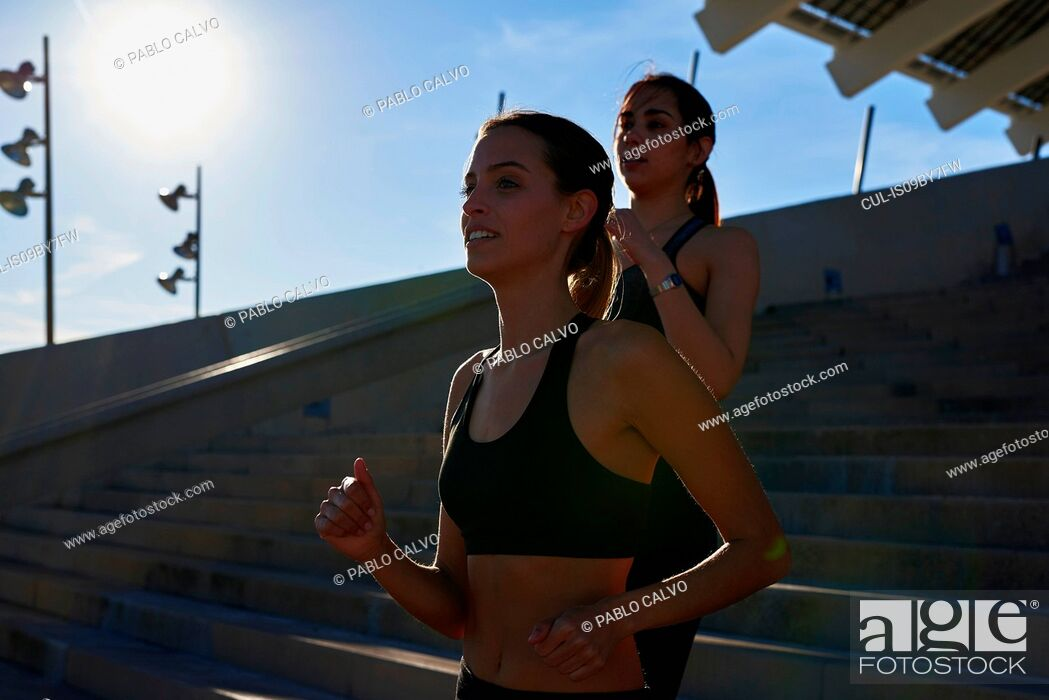 Stock Photo: Friends jogging down steps in sports stadium.