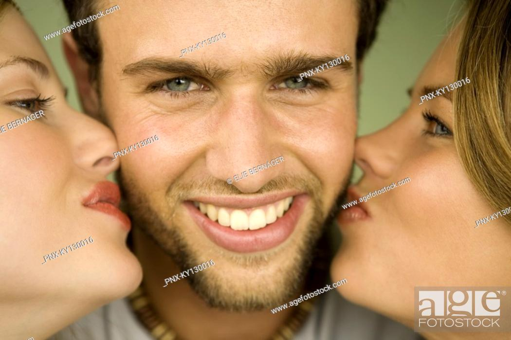 Stock Photo: 2 young women kissing smiling man.