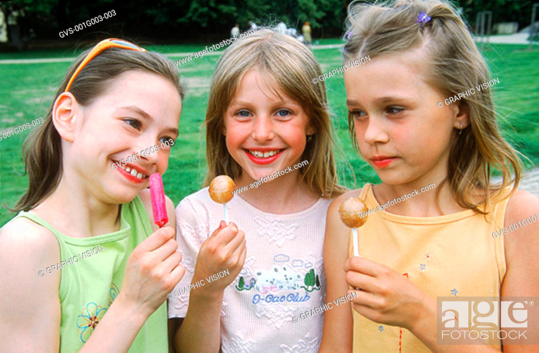 Stock Photo: Young girls smiling holding lollipops.