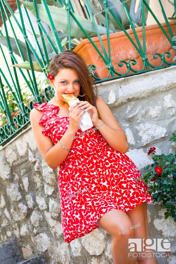 Stock Photo: Pretty young-adult girl is eating sandwich seductively smiling at camera.