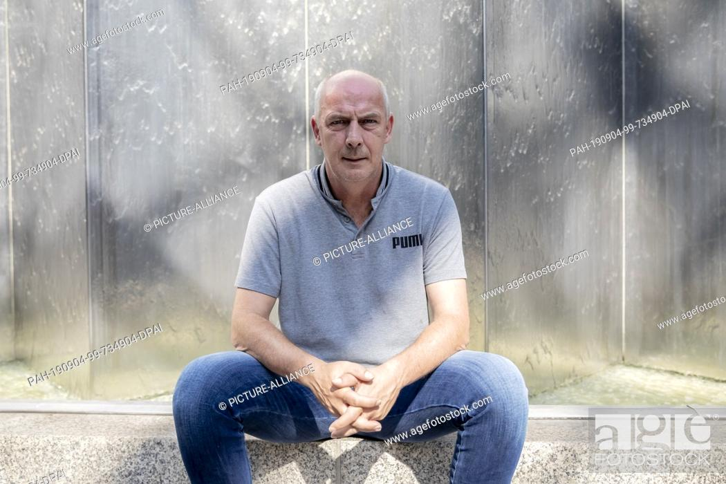 Stock Photo: 27 August 2019, Berlin: Mario Basler, former professional soccer player, is sitting in front of a water wall in the courtyard of a hotel in front of an.
