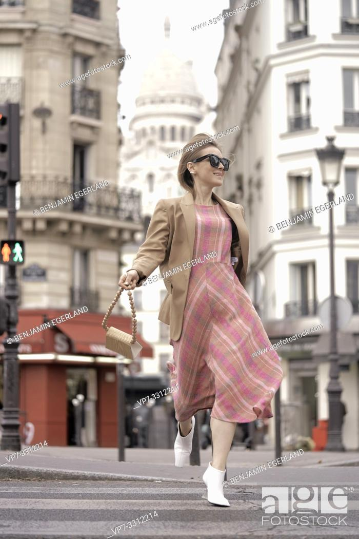 Stock Photo: fashionable blogger woman running at street in front of touristic sight Basilica Sacré-Cœur, during fashion week, in city Paris, France.