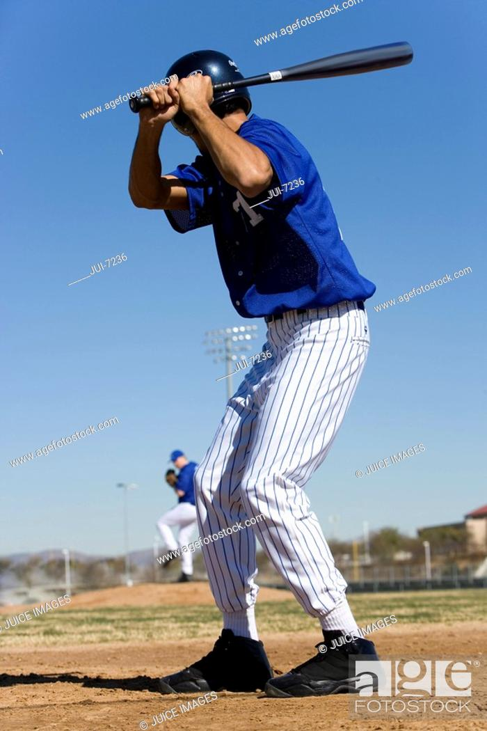 Stock Photo: Baseball batter facing pitcher during competitive game, focus on foreground, rear view.