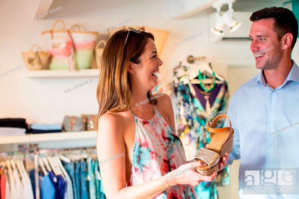 Stock Photo: Young woman tempting boyfriend to buy sandals in boutique, Majorca, Spain.