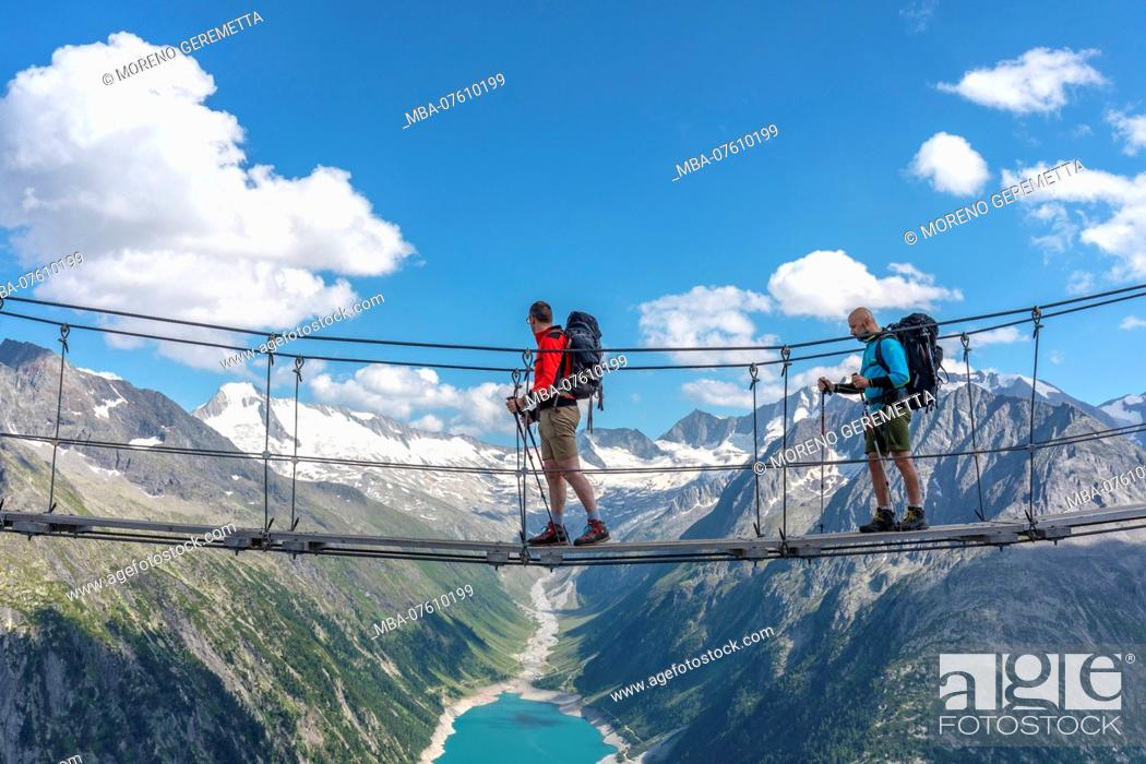 Stock Photo: Two hikers on the tibetan bridge near Olperer hut with Schlegeis Stausee on the background, Zillertal Alps, Tyrol, Schwaz district, Austria.