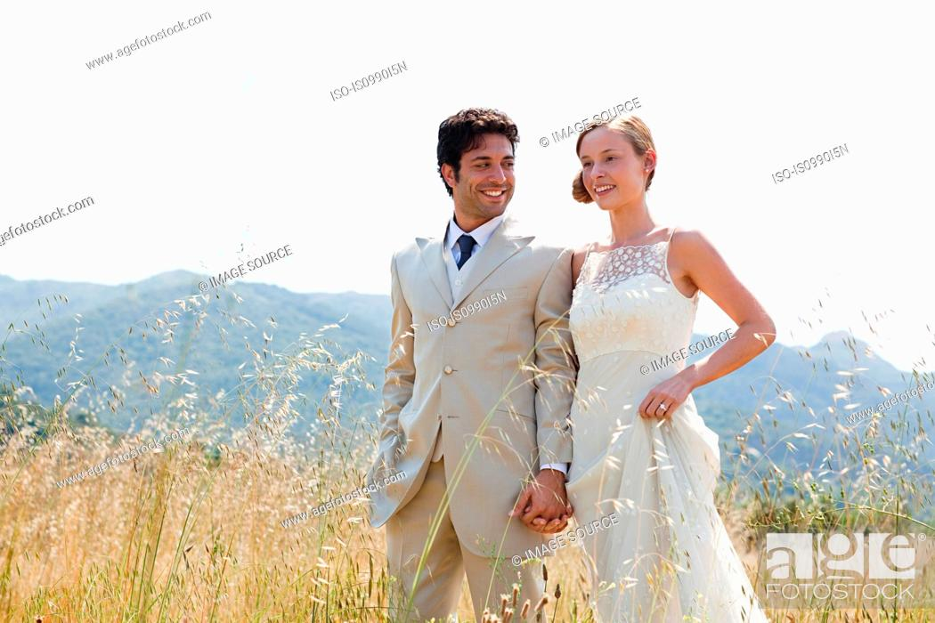 Stock Photo: Newlyweds walking in field, holding hands.