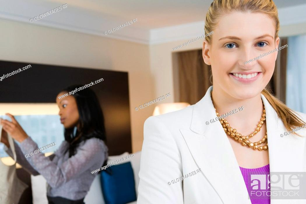 Stock Photo: Portrait of a businesswoman smiling with another businesswoman standing in the background.