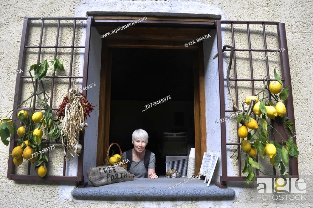 Stock Photo: A visitor peeks out of the window of a small cafe in the countryside near Scala, the Amalfi Coast, Italy. Fresh lemons and drying herbs, all locally produced.