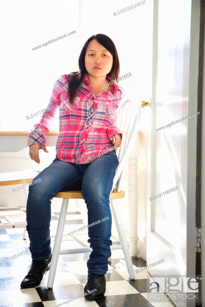 Stock Photo: Woman sitting on chair at table in kitchen.