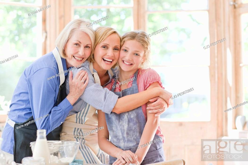 Stock Photo: Smiling multi-generation females hugging in kitchen.
