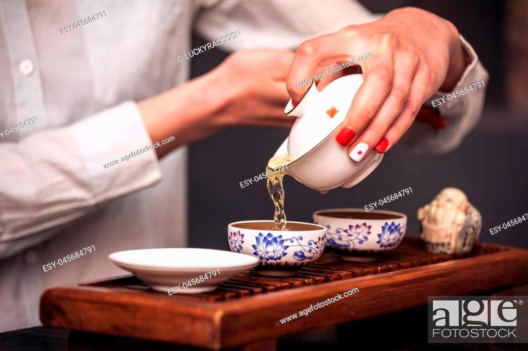 Stock Photo: Cropped shot of woman pouring teacup in traditional chinese teaware.