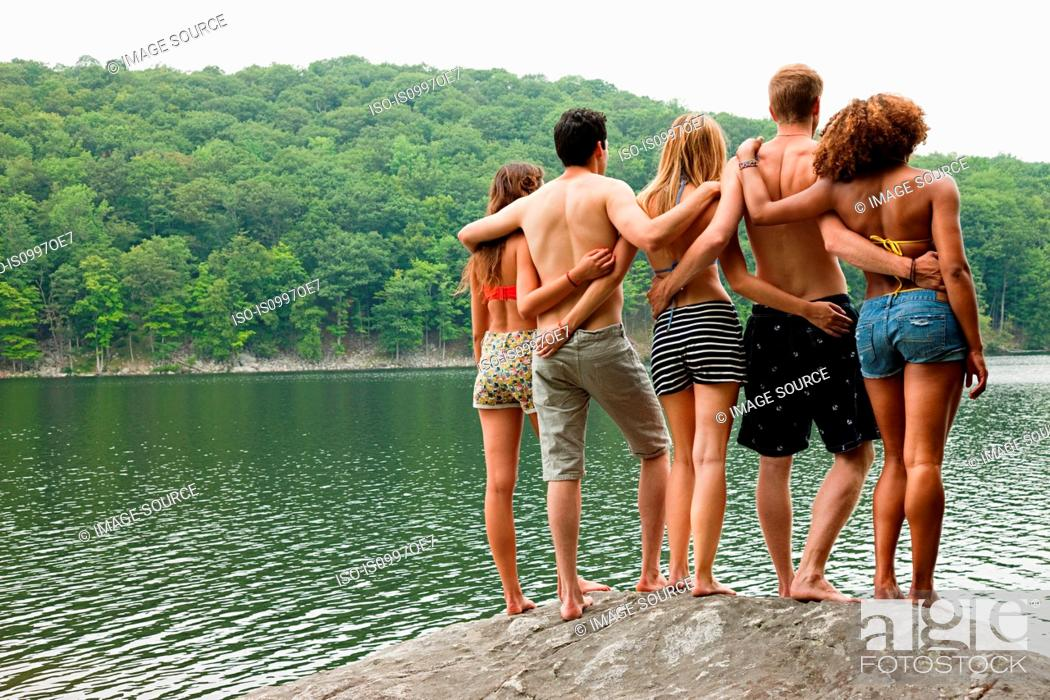 Stock Photo: Friends standing together on rock at lakeside.