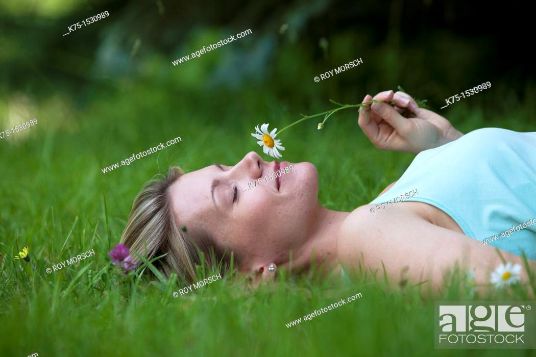 Stock Photo: Woman lying on lawn smelling a daisy.