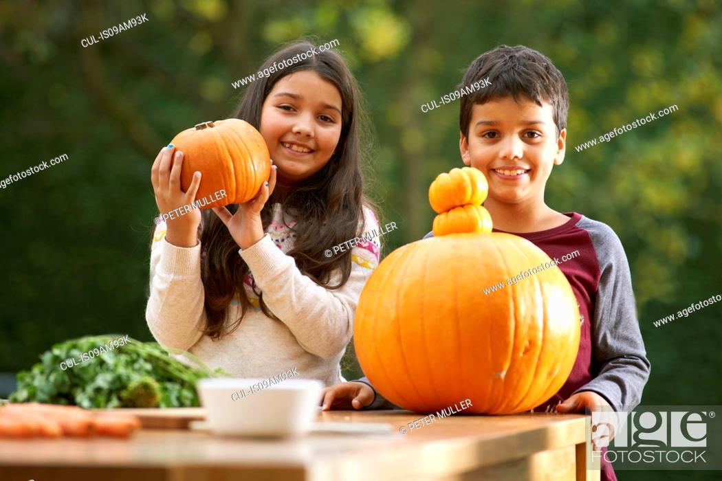 Stock Photo: Portrait of brother and sister in garden holding up a pumpkin.