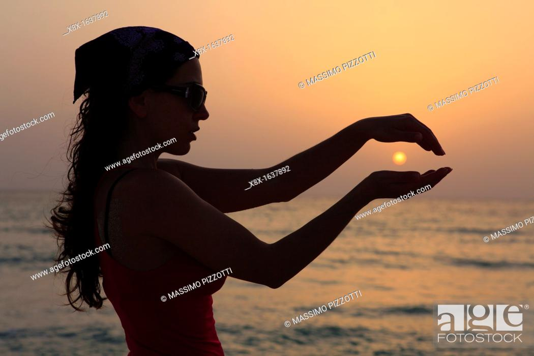Stock Photo: Sihouette of a woman holding the sun.