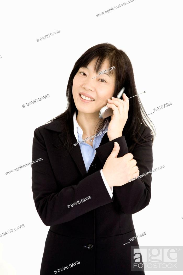 Stock Photo: Beautiful Asain Businesswoman talking on a cell phone on a white background.