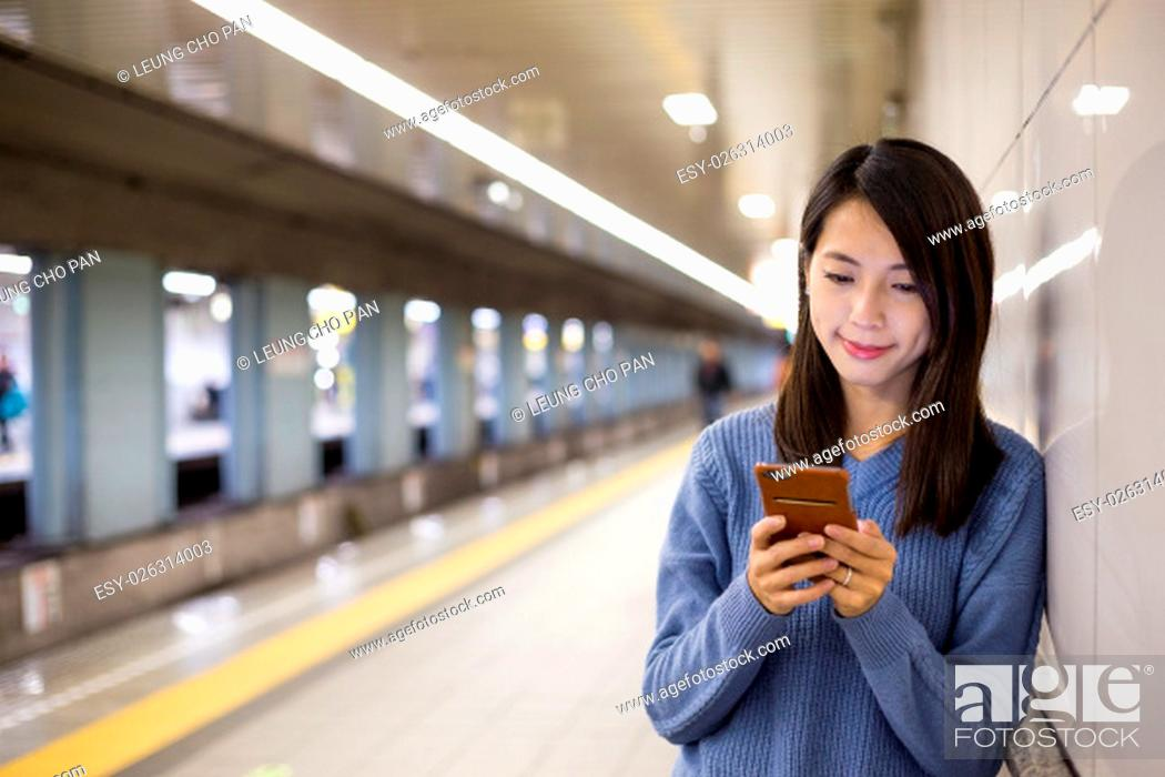 Stock Photo: Woman use of cellphone in underground metro station.