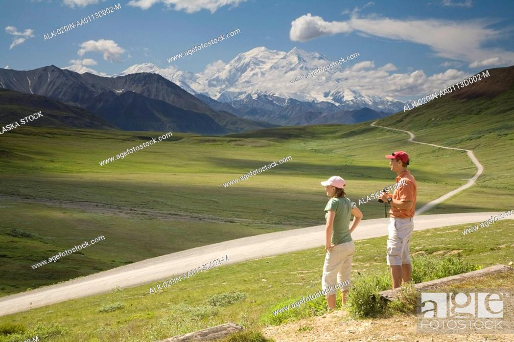 Photo de stock: Young couple of tourist view Mt.McKinley and the Alaska Range from Stony Hill overlook in Denali NP Alaska summer.