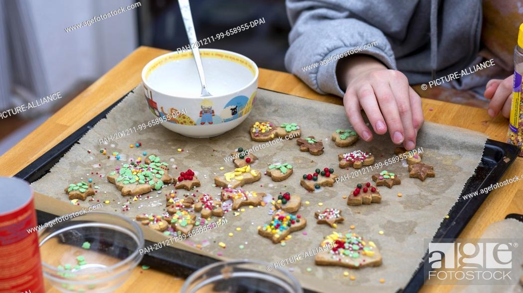 Stock Photo: 10 December 2020, Saxony-Anhalt, Magdeburg: A girl decorating Christmas cookies. Photo: Stephan Schulz/dpa-Zentralbild/ZB.