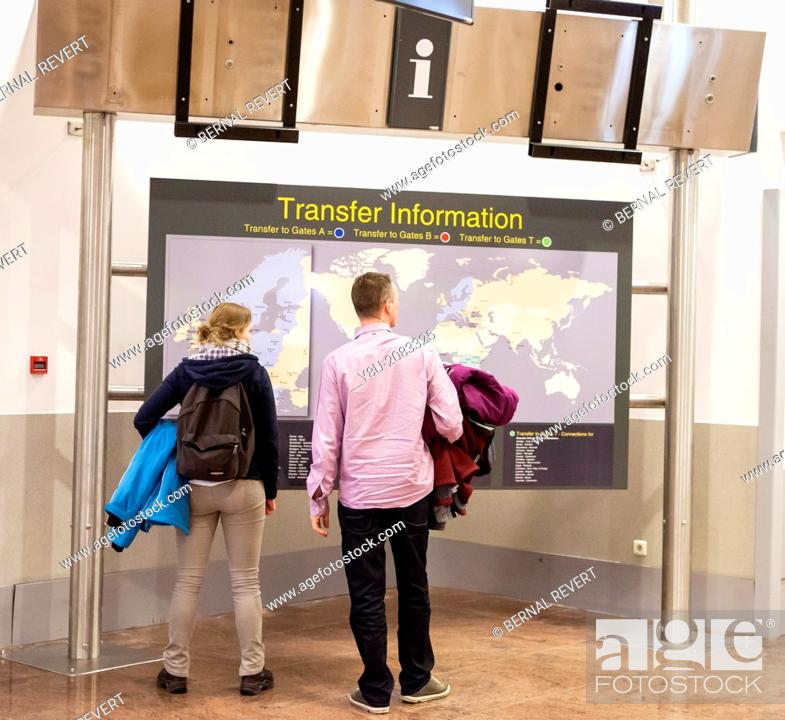 Stock Photo: Two people checking the transfer information sign at Brussels airport.
