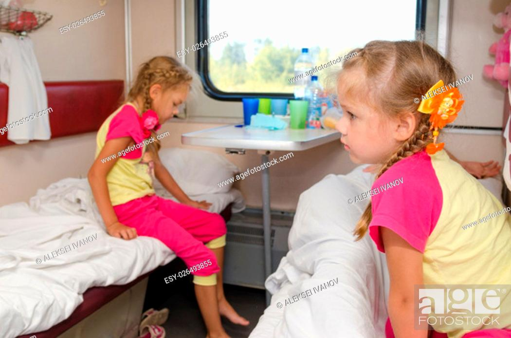 Stock Photo: Two girls sisters on the train on the lower ground in the second-class compartment wagon.