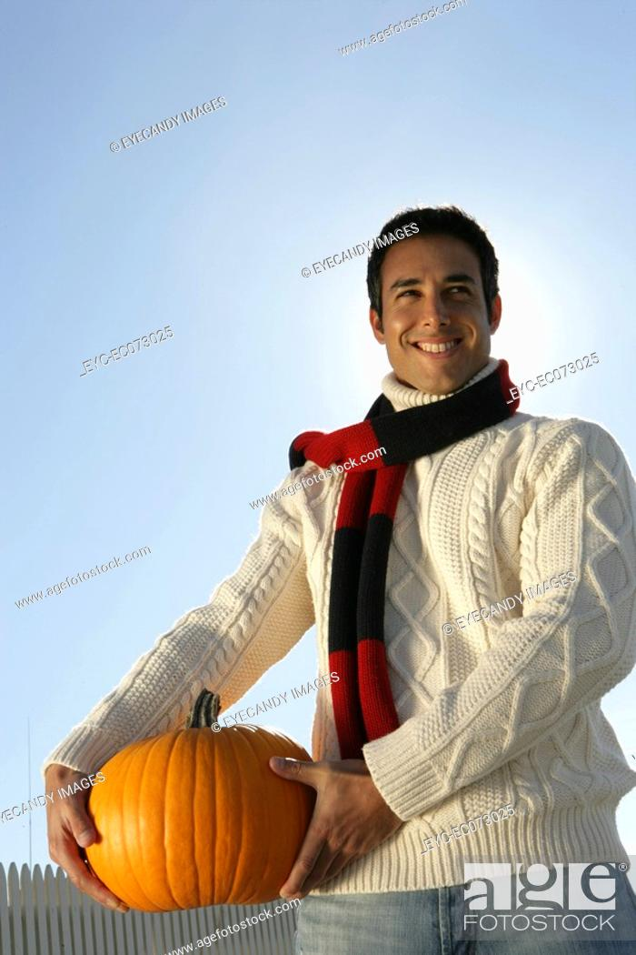 Stock Photo: Young man holding pumpkin.