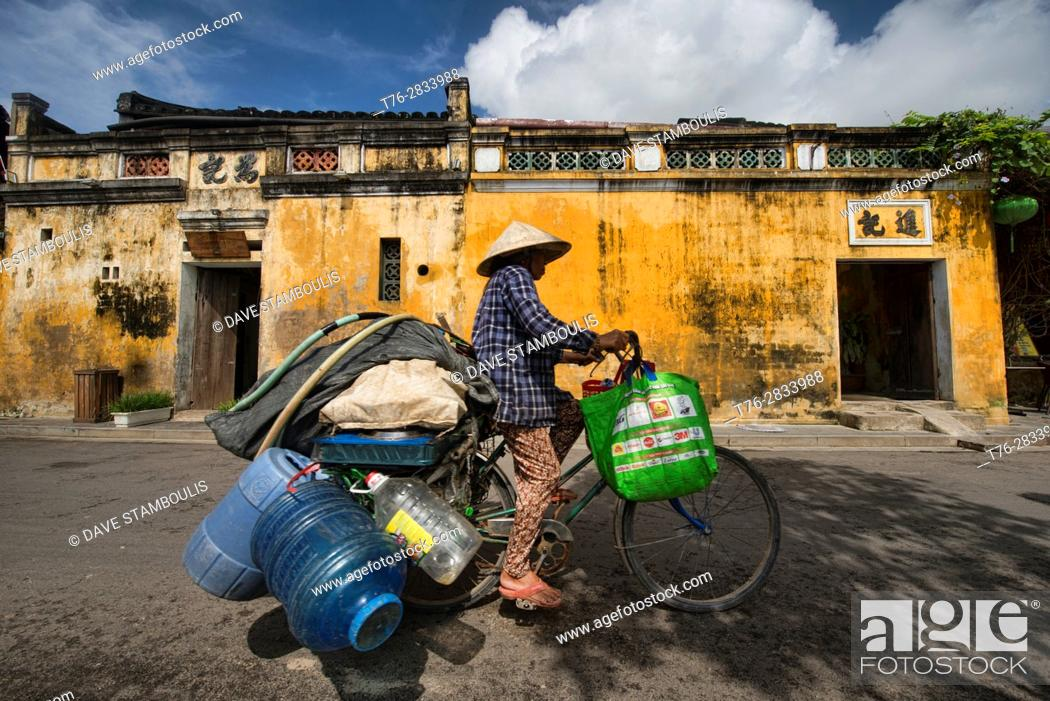 Stock Photo: Bicycling with a load in the picturesque old town of Hoi An, Vietnam.