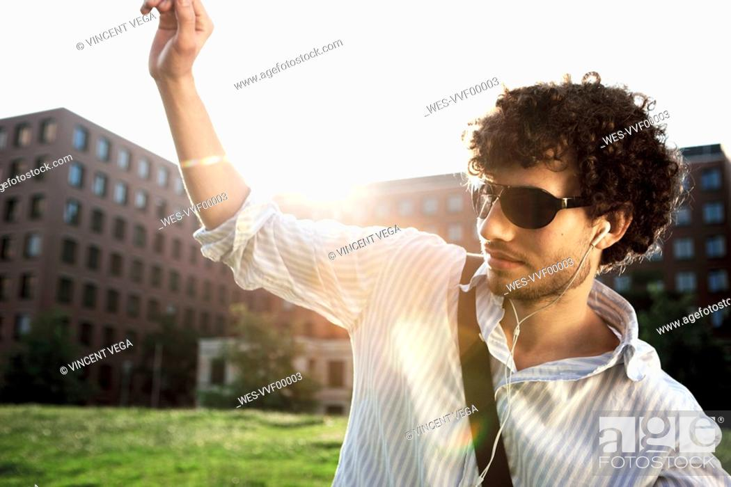 Stock Photo: Germany, Berlin, Young man listening to MP3-Player.