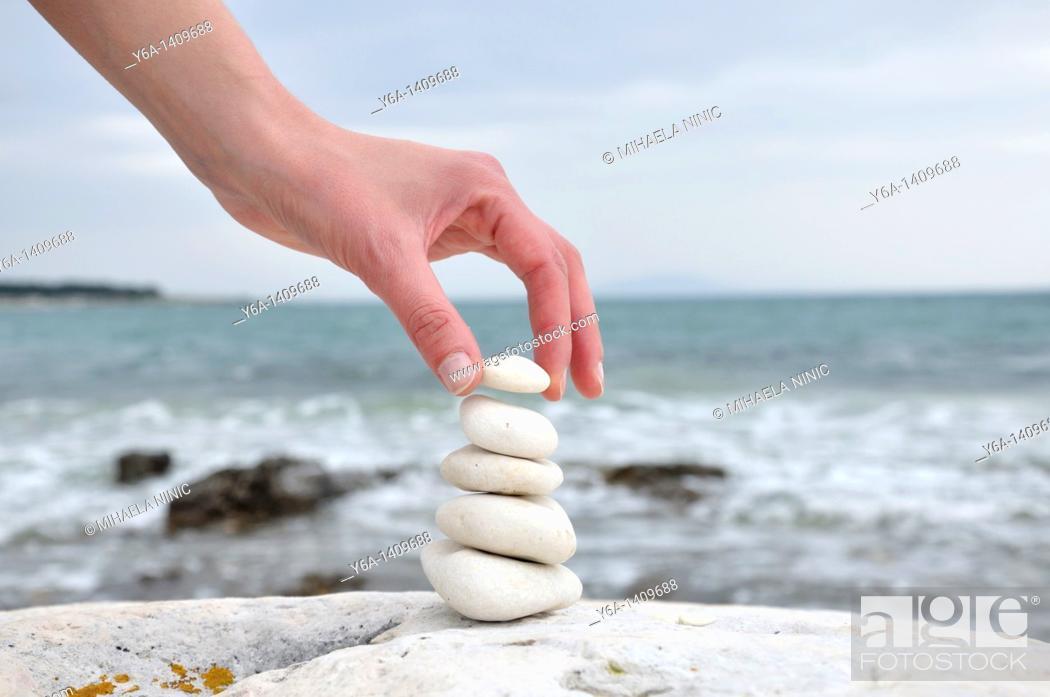 Stock Photo: Woman stacking stones on beach.