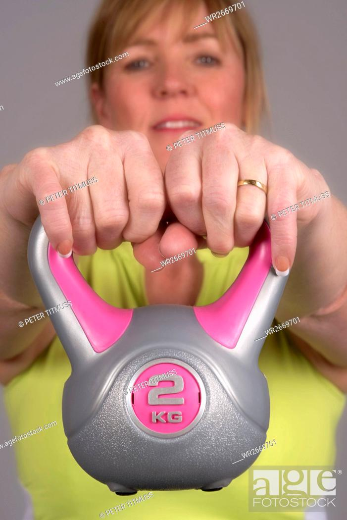 Stock Photo: Woman exercising with a kettle bell weight.