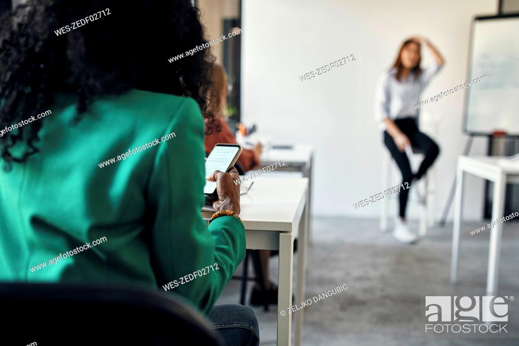 Stock Photo: Businesswoman using smartphone during workshop in conference room.