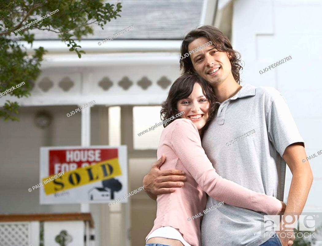 Stock Photo: Man and woman embracing in front of house with sold sign.