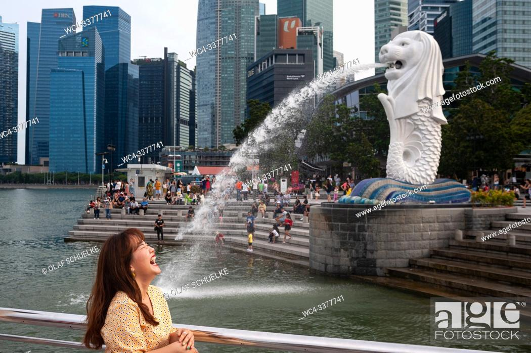 Stock Photo: Singapore, Republic of Singapore, Asia - A female tourist poses for photos in the Merlion Park along the Singapore River with the Central Business District in.