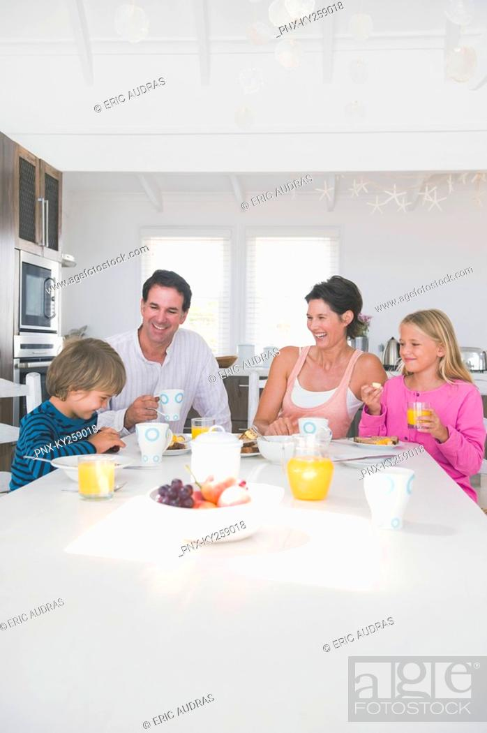 Stock Photo: Family having breakfast at the dining table.