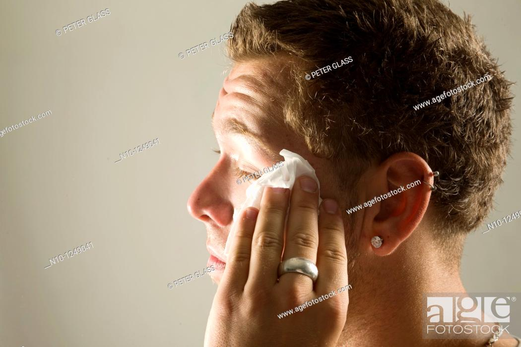 Stock Photo: Young man wiping his face with a paper towel.
