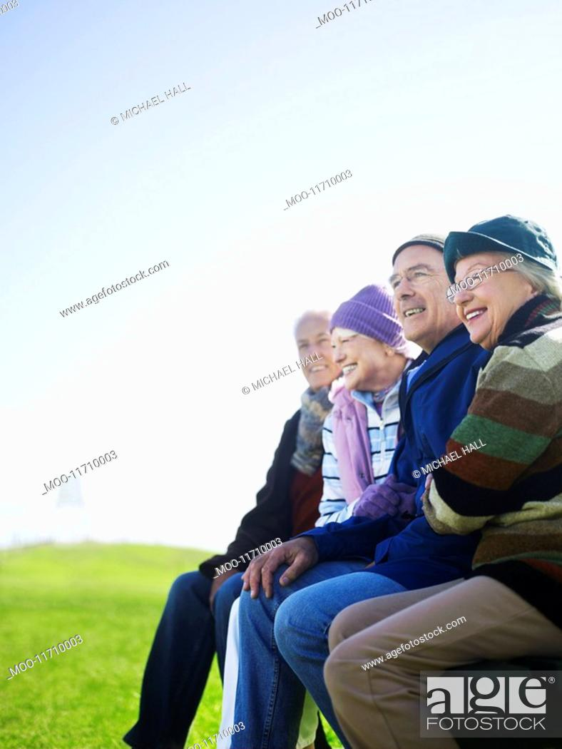 Stock Photo: Four senior friends sitting outdoors laughing.