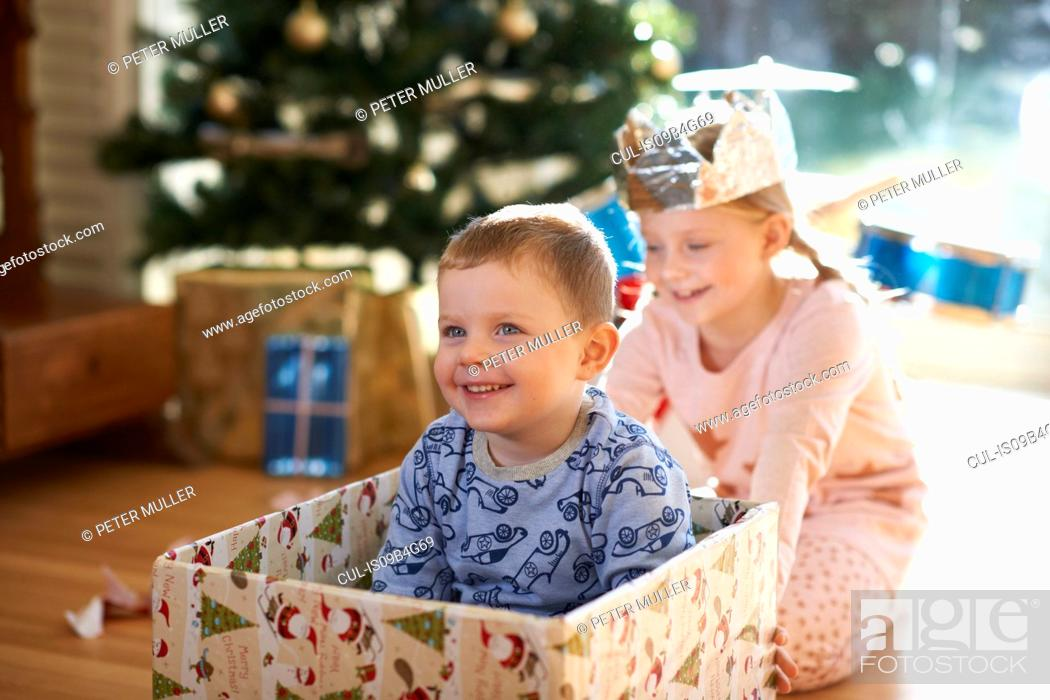 Stock Photo: Girl pushing brother in cardboard box at christmas.