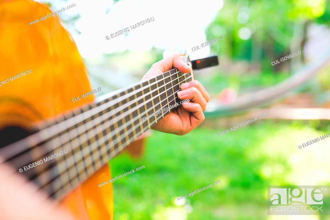 Stock Photo: Man's hands playing acoustic guitar in garden.