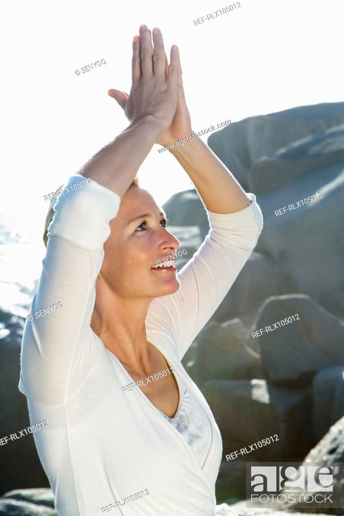 Stock Photo: Mature woman arms raised above her head doing Yoga exercises, side profile.