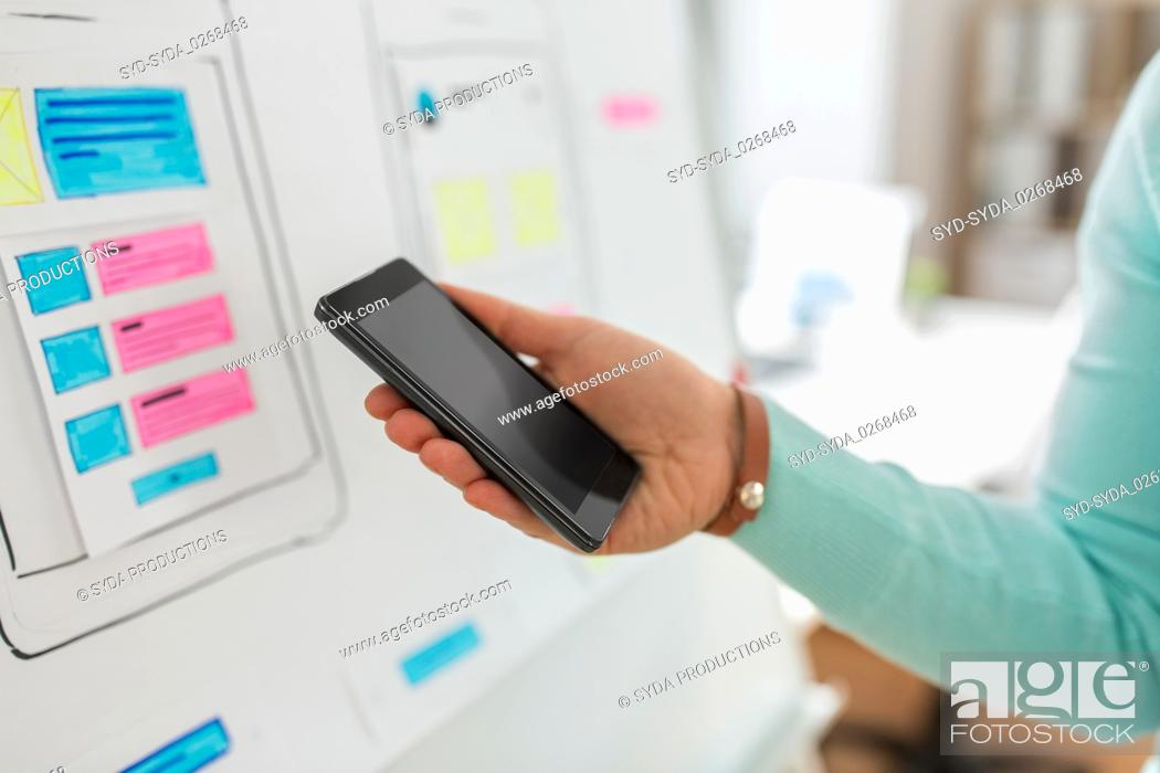 Stock Photo: ui designer or developer hand holding smartphone.