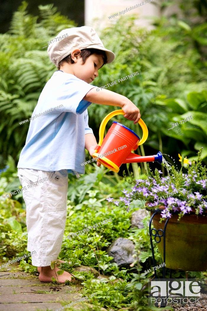 Stock Photo: Toddler is watering plants in the garden.