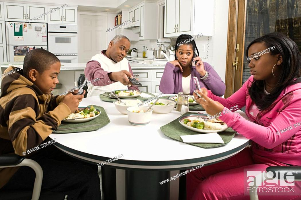 Stock Photo: Distracted family at the dinner table.