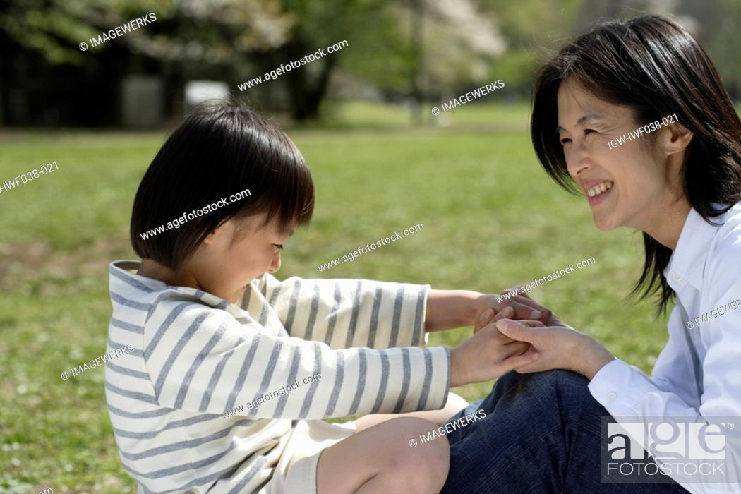 Stock Photo: Mother and daughter playing in garden.