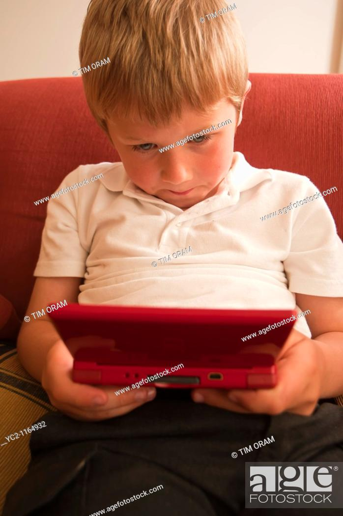 Stock Photo: A  close up picture of a six year old boy playing on a nintendo DS handheld computer game console in the Uk.
