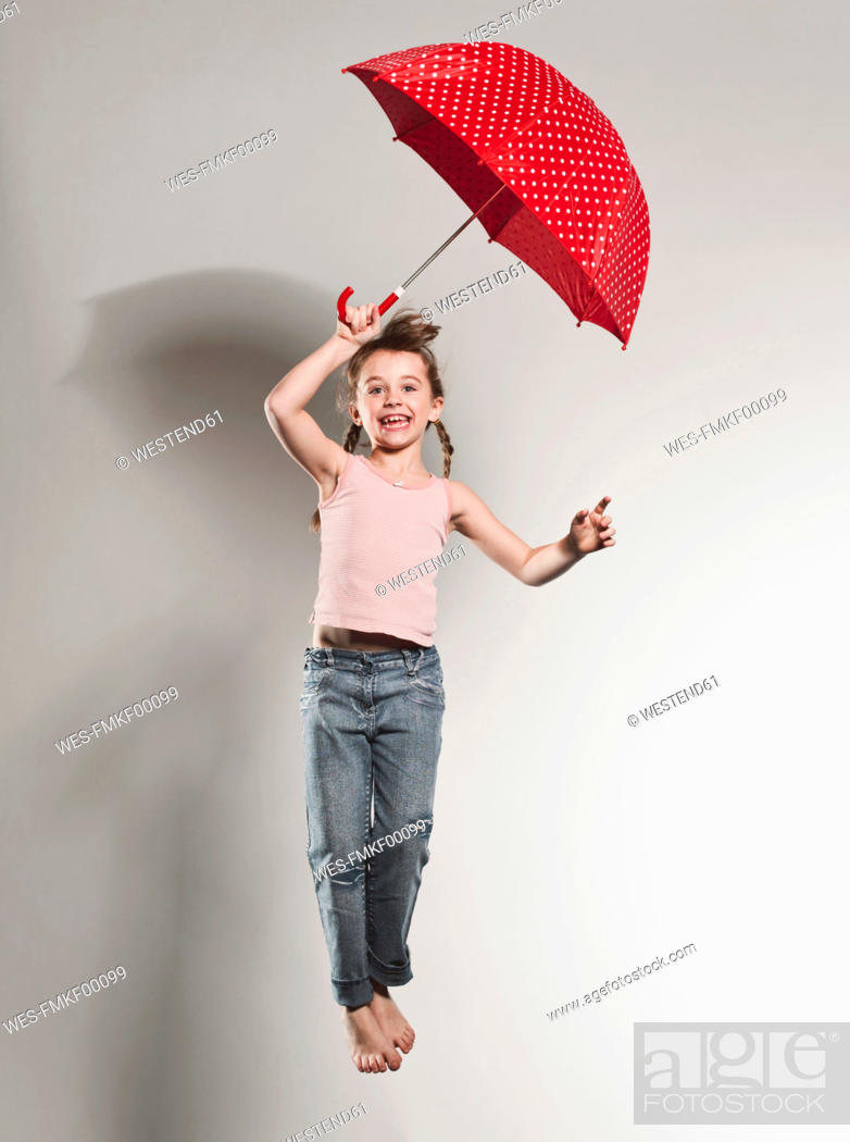 Stock Photo: Girl 6-7 jumping with holding umbrella, smiling, portrait.