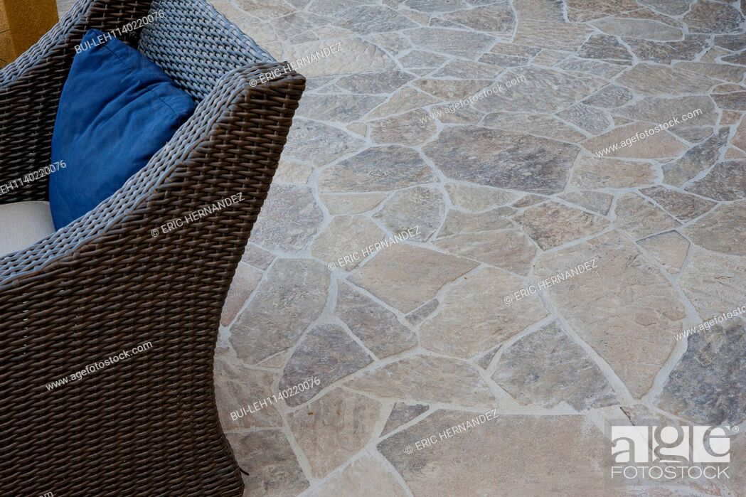 Imagen: Close-up of stone floor with cropped wicker chair.