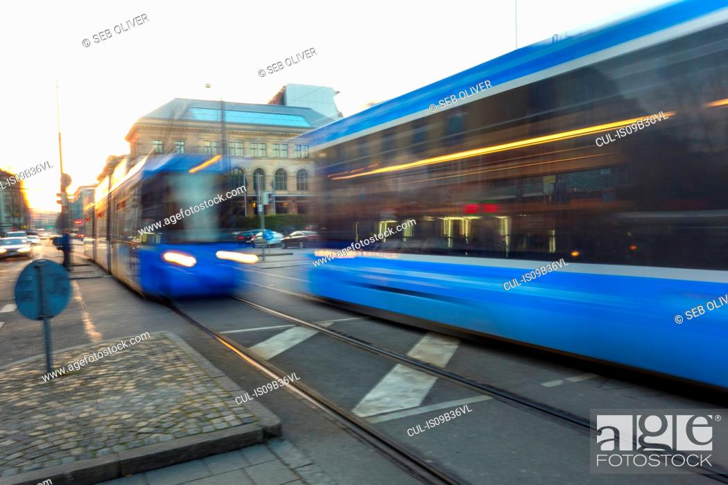 Stock Photo: Blue trams passing in opposite directions in city, blurred motion.
